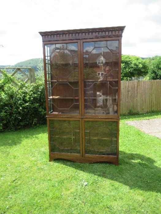 A Georgian design display cabinet, having astragal glazed doors to the upper and lower sections,
