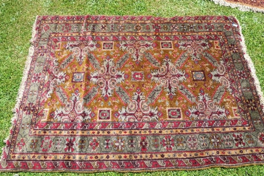 A modern Eastern rug, decorated with repeating symbols and leaves to a gold ground field and green