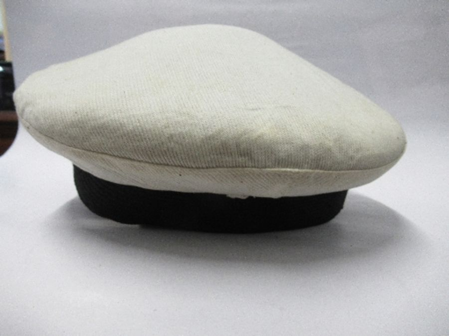 A British naval style visor cap in white cotton, with anchor and crown to the front on a black hat - Image 4 of 13