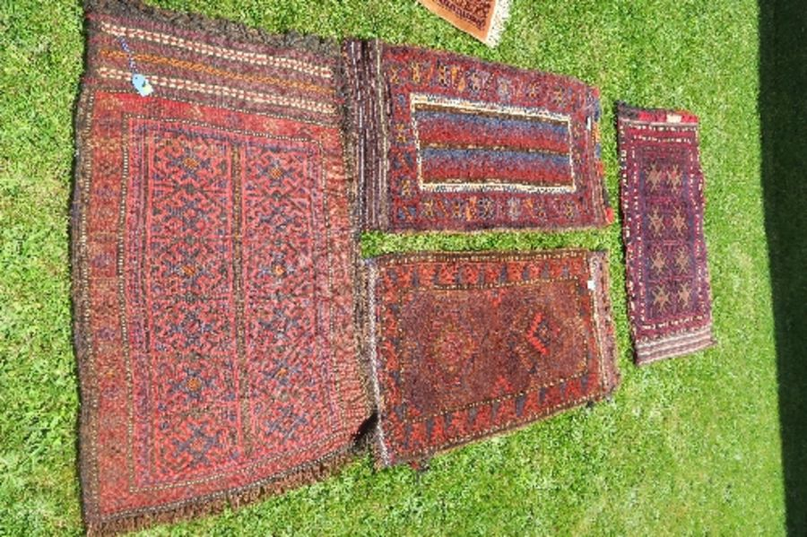 Four Eastern mats, all decorated with different designs to a red ground, all approximately 20ins x