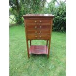 An Edwardian mahogany music cabinet, having four drawers, with drop down front, raised on square
