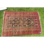 An Eastern prayer rug, the field decorated with repeating symbols, the borders with red ground,