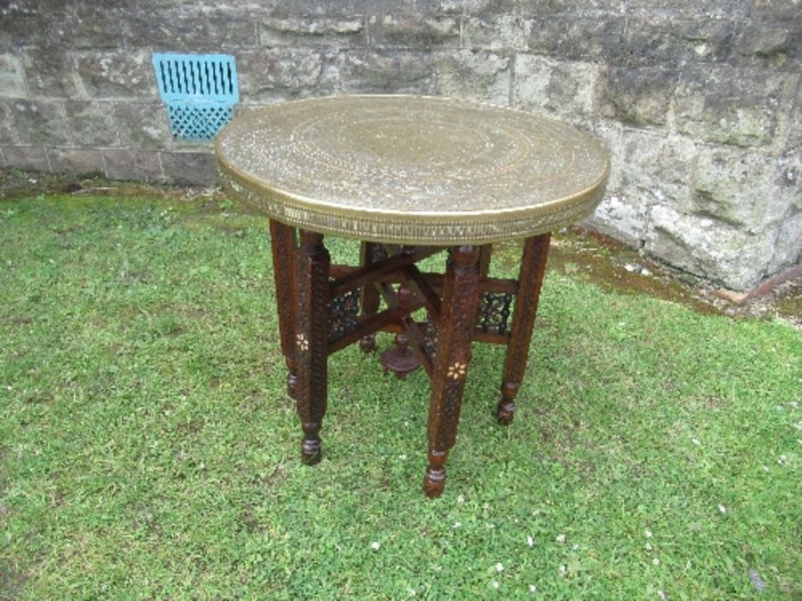 A brass Benares topped table, the wooden folding base with carved and inlaid decoration, diameter