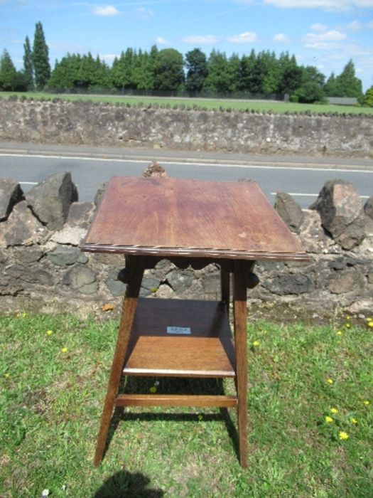 An Arts and Crafts style square topped side table, raised on outswept legs united by a shelf,