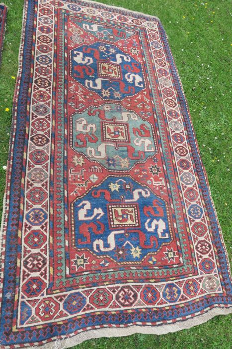 An Eastern style rug, the blue ground field having repeating motifs, 48ins x 95ins, together with