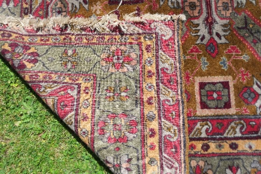 A modern Eastern rug, decorated with repeating symbols and leaves to a gold ground field and green - Image 2 of 2