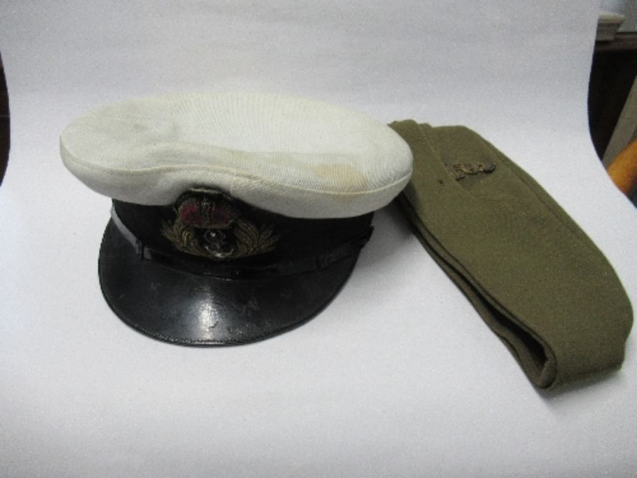 A British naval style visor cap in white cotton, with anchor and crown to the front on a black hat