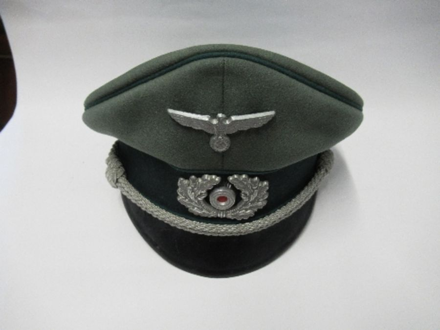 A Third Reich style visor cap, in green felt fabric with dark green piping and hat band, silver