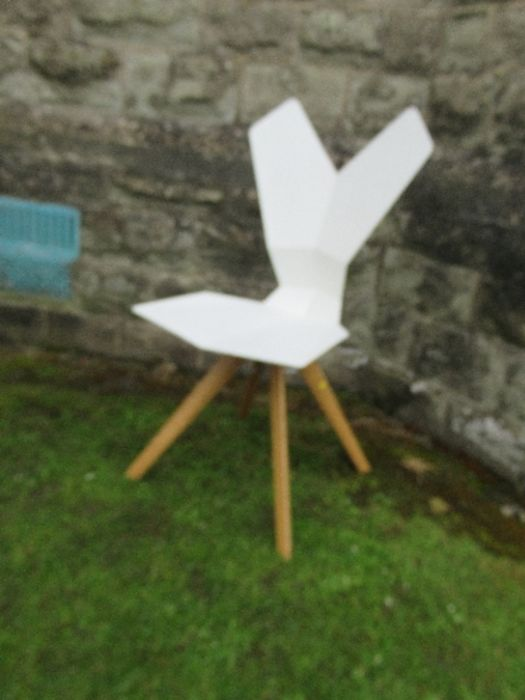 A white plastic chair with geometric shaped back and seat raised on metal chairs