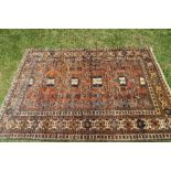 An Eastern design rug, decorated with repeating motifs to an orange ground, 52ins x 76ins