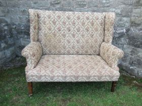 A high backed wing back two seater settee, the floral upholstery, width 53ins x height 47ins