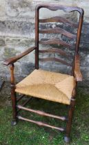 A 19th century Lancashire ladder back open armchair, with rush seat
