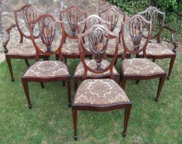 A set of eight (6+2) mahogany shield back dining chairs, with carved, pierced and inlaid