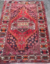 An Eastern style rug, the red ground decorated with repeating symbols, 55ins x 80ins