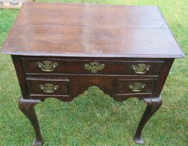 An Antique oak lowboy, fitted one long drawer and two short drawers, raised on cabriole legs and pad