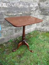 A mahogany occasional table, having rectangular top raised on a turned column, terminating in out