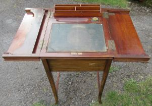 An Edwardian mahogany writing desk, the top fitted with a pair of hinged flaps, opening to reveal