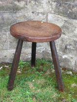 An Antique cricket style table, with circular top and raised on three legs, diameter 16ins, height