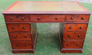 A 19th century mahogany pedestal desk, with tooled leather writing surface, having an arrangement of