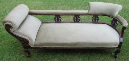 A late 19th century mahogany and upholstered chaise longue, with pierced carved uprights, raised