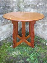 An Arts & Crafts oak Hispanic style circular lamp table, in the style of Sir Peter Lorimer, with