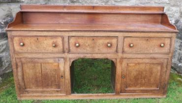 An antique oak Welsh sideboard, with three drawers to the frieze, above cupboard doors to each side,