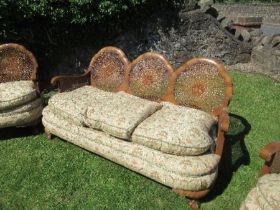 A walnut framed bergere suite, comprising a three seat sofa width 67ins x height 31ins, and two