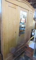 A pine mirror door wardrobe, fitted with two drawers to the base, width 66ins, height 80ins