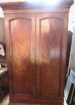 A Victorian mahogany double door wardrobe, fitted with a hanging space and drawer to one side,