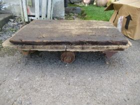 A wooden trolley, raised on wrought iron wheels, af