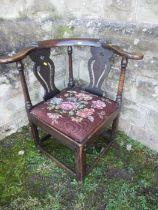 An Antique oak corner chair, with pierced splats