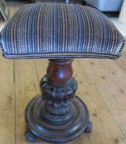 A Victorian mahogany adjustable piano stool, with square upholstered top, on carved column and