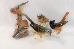 A collection of ceramic bird figures and groups including a Royal Worcester porcelain bird group