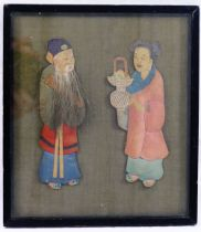 An early 20th century Chinese fabric covered panel mounted in relief with a pair of painted fabric,