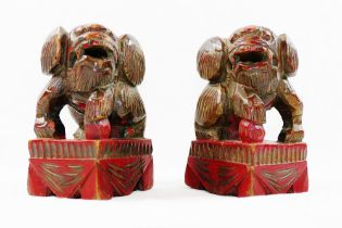 A small pair of Chinese carved wooden temple dogs of foo, painted in red and gilt, on square bases,