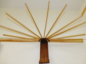 An early 20th century wall mounted folding airer, the 10 sticks each 54cm long,