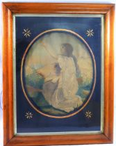 A 19th century oval embroidered silk picture of a young woman kneeling with her arms aloft,