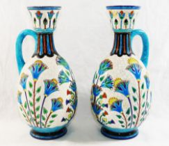 A pair of French Lonwy Pottery ewers, with stylised floral enamel decoration,