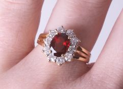 An 18ct diamond and garnet cluster ring, size M.