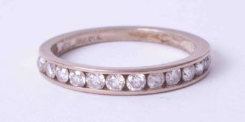 An 18ct half band channel set diamond eternity ring, size L.