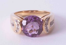 A modern 9ct yellow gold ring with tension set amethyst and diamond detail on the shoulders,