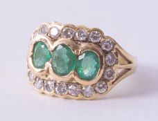 An 18ct emerald and diamond cluster ring, set with three oval cut emeralds, surrounded by eighteen