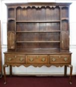 An oak dresser of Georgian design, in two sections, the upper part with open shelves and