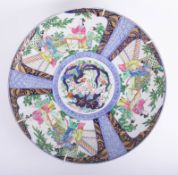 An oriental porcelain charger decorated with panels of figures, exotic birds, gilt work on a blue