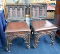 Two heavily carved dark oak side chairs.