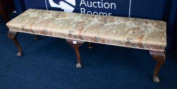 A long upholstered stool, six legs.
