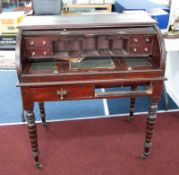 A Victorian mahogany cylinder writing desk together with a mirror.