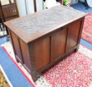 A small lined blanket chest with carved top.