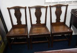 A set of carved oak dining chairs with hard seats.