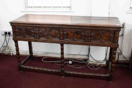 An early 20th century oak low dresser fitted with drawers with geometric mouldings and turned legs.